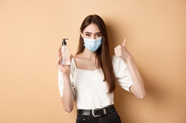 Covid-19 i koncepcja środków zapobiegawczych. uśmiechnięta dziewczyna w masce medycznej pokazuje kciuk w górę i środek dezynfekujący do rąk, polecam produkt do dezynfekcji, beżowe tło.