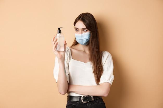 Covid-19 i koncepcja środków zapobiegawczych. uśmiechnięta dziewczyna w masce patrzy na butelkę odkażacza do rąk, używając produktu higienicznego z epidemii koronawirusa, beżowe tło.