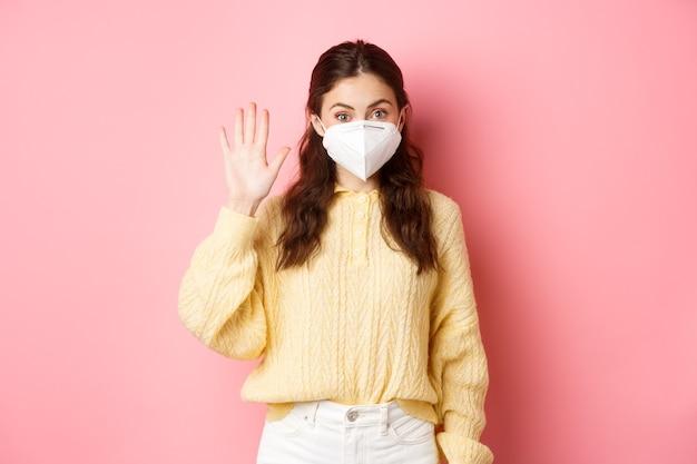 Covid-19, koncepcja blokady i pandemii. młoda kobieta ubrana w maskę podczas kwarantanny, wita się, macha podniesioną ręką, aby pozdrowić osobę z daleka, różowa ściana.