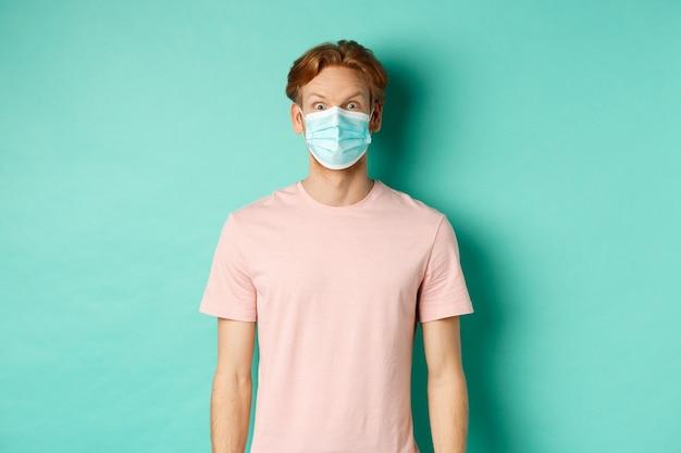 Covid-19, koncepcja dystansu społecznego i kwarantanny. młody mężczyzna unoszący brwi i wyglądający na zaskoczonego, noszący maskę podczas pandemii, stojący na miętowym tle.