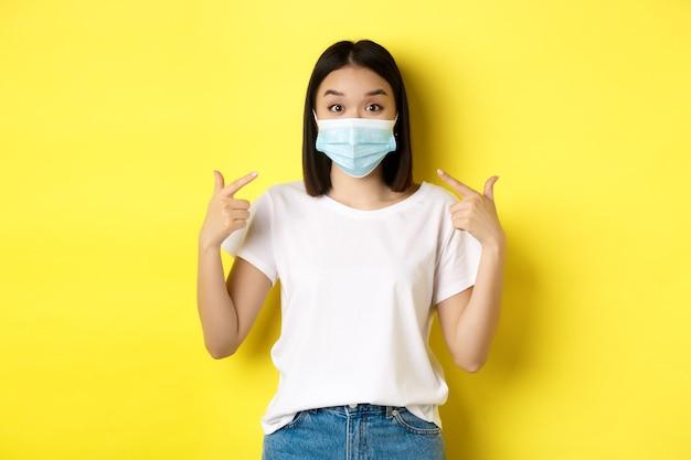 Covid-19, koncepcja kwarantanny i dystansu społecznego. młoda azjatka w białej koszulce, wskazująca na swoją maskę medyczną z koronawirusa, żółte tło.