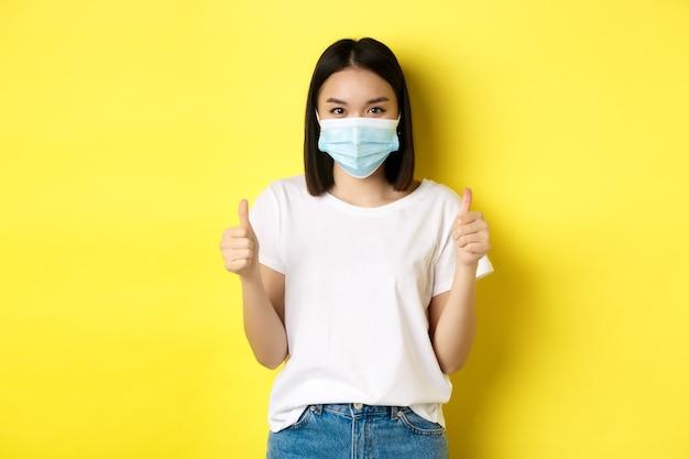 Covid-19, koncepcja kwarantanny i dystansu społecznego. wesoła azjatykcia kobieta w masce medycznej i białej koszulce pokazuje kciuki do góry z aprobatą, chwalę dobrą ofertę, żółte tło.