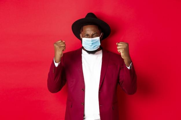 Covid-19, koncepcja kwarantanny i wakacji. wesoły afroamerykanin pokazujący zaciśniętą pięść i radujący się z wygranej, osiągnięcia celu, noszący maskę medyczną od koronawirusa