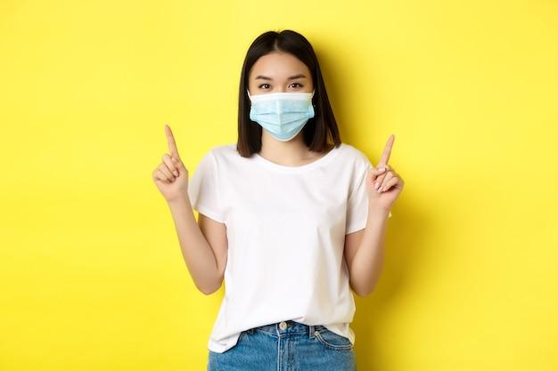 Covid-19, koncepcja pandemii i dystansu społecznego. młoda azjatka w białej koszulce i masce medycznej z koronawirusa, wskazująca palcami w górę, pokazująca specjalną ofertę.