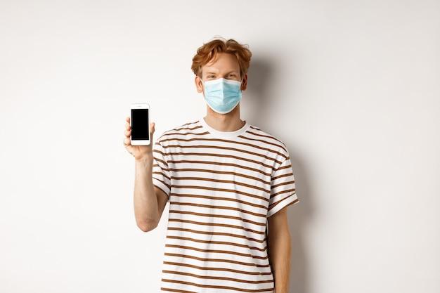 Covid-19, koncepcja pandemii i dystansu społecznego. przystojny młody człowiek z maską, pokazując czarny ekran smartfona i uśmiechnięty, stojący na białym tle.