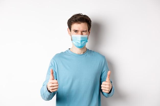 Covid-19, koncepcja pandemii i dystansu społecznego. szczęśliwy młody człowiek w masce medycznej mrugając, pokazując kciuki z aprobatą, polecając produkt, białe tło.