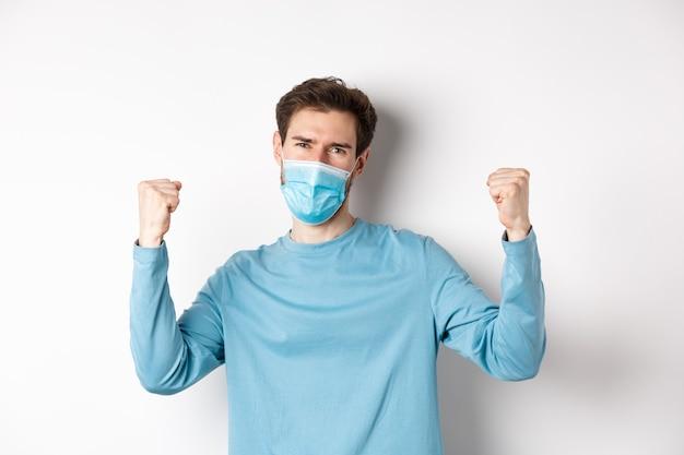 Covid-19, koncepcja pandemii i dystansu społecznego. szczęśliwy młody człowiek w masce medycznej, wygrywając, krzycząc tak z satysfakcją i podnosząc ręce, świętując zwycięstwo, białe tło.