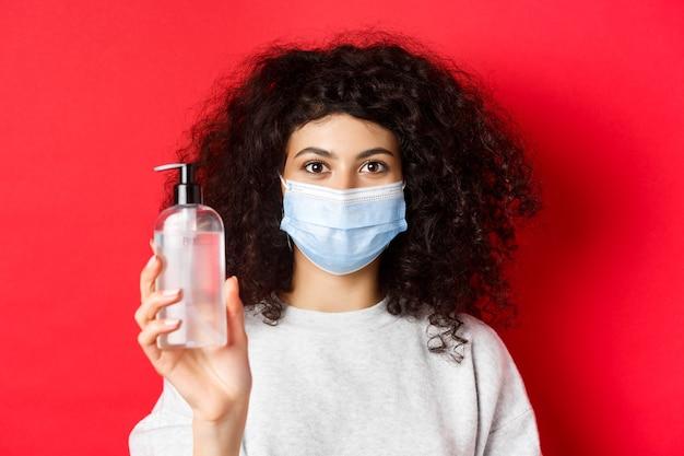Covid-19, koncepcja pandemii i kwarantanny. młoda kobieta w masce medycznej pokazuje butelkę odkażacza do rąk, demonstruje działanie antyseptyczne, czerwone tło.