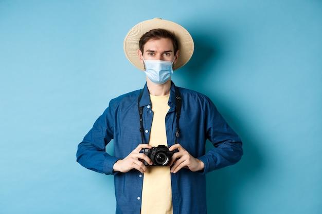 Covid-19, koncepcja pandemii i podróży. młody facet podróżujący za granicę z aparatem, robiąc zdjęcia na wakacjach, w masce medycznej z koronawirusa, niebieskie tło.