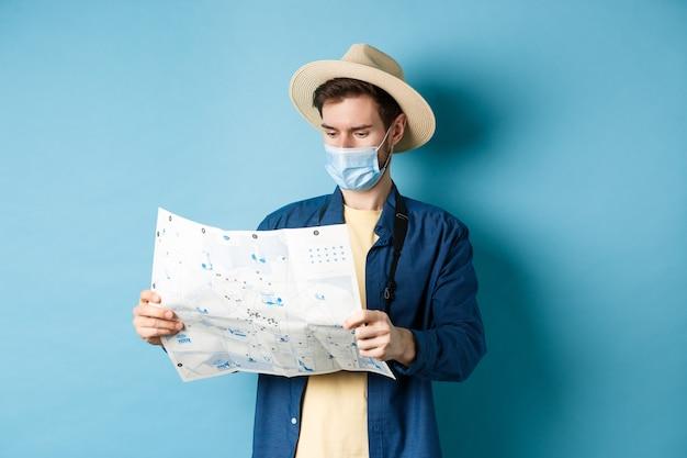 Covid-19, koncepcja pandemii i podróży. turysta patrząc na mapę ze zwiedzaniem na wakacjach, ubrany w letni kapelusz i maskę medyczną z koronawirusa, niebieskie tło.