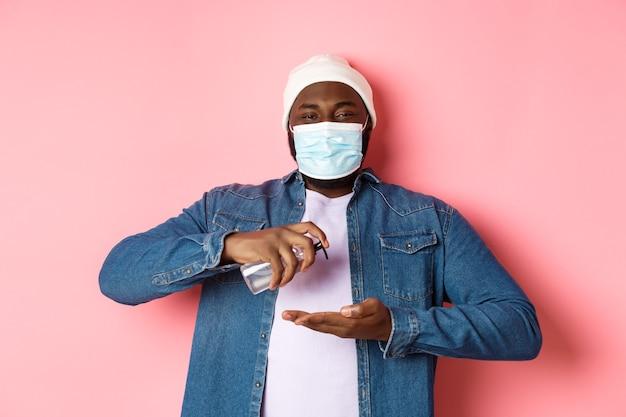 Covid-19, koncepcja stylu życia i blokady. uśmiechnięty mężczyzna afro-amerykański w masce do czyszczenia rąk środkiem dezynfekującym, za pomocą środka antyseptycznego i patrząc na kamery, różowe tło.