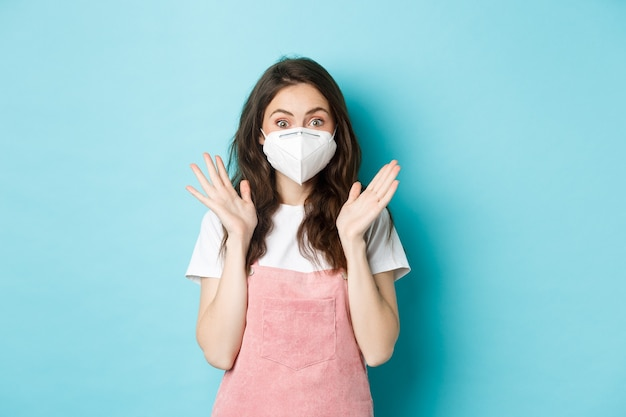 Covid-19, koncepcja szczepień i kwarantanny. podekscytowana i zaskoczona młoda kobieta w respiratorze medycznym, maska na twarz od koronawirusa, klaskanie w dłonie i zdumiona kamera, niebieskie tło