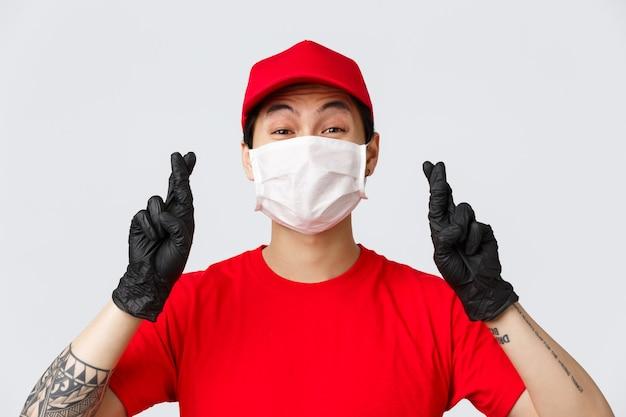 Covid-19, koncepcja zakupów online poddająca się kwarantannie. kurier pozostaje pozytywnie nastawiony do pandemii koronawirusa, modląc się o bezpieczeństwo klientów. facet dostarczający skrzyżowane palce, nosić maskę medyczną i rękawiczki, skrzyżować palce