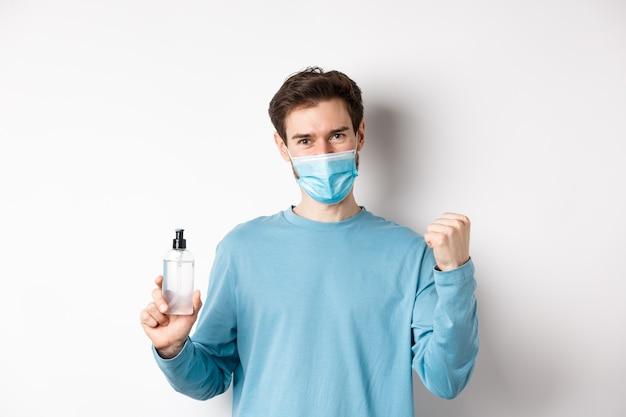 Covid-19, koncepcja zdrowia i kwarantanny. wesoły mężczyzna w masce na twarz świętuje, pokazując pompkę pięścią i butelkę ze środkiem dezynfekującym do rąk, walcząc z zarazkami, białe tło.