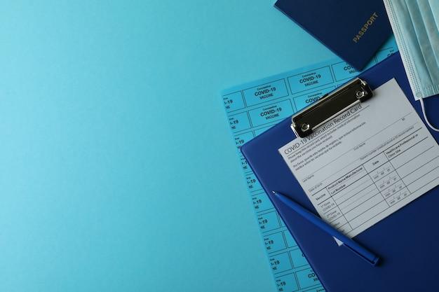 Covid - 19 koncepcji szczepień z kartą rejestracyjną, maską i paszportem na niebieskim tle