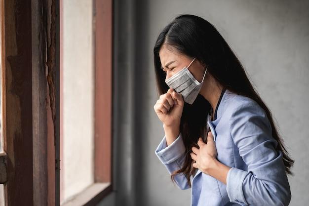 Covid-19 koronawirus pandemiczny, azjatycka kobieta ubrana w maskę, ma objawy kaszlu i gorączki
