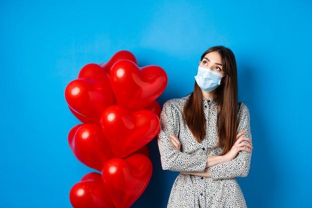 Covid-19, kwarantanna i koncepcja zdrowia. marzycielska piękna dziewczyna w masce na twarz i sukience, patrząc na zamyślony w lewym górnym rogu, stojąca w pobliżu balonów walentynkowych, niebieskie tło