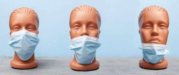 Covid 19, maska medyczna na manekinie, jak poprawnie założyć instrukcje na niebieskim tle