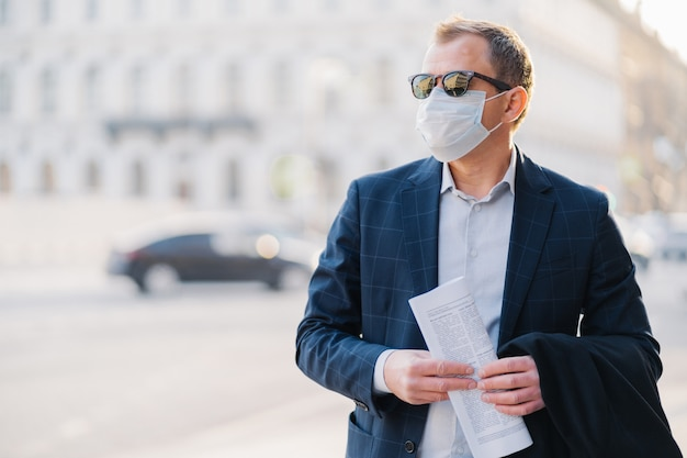 Covid-19. mężczyzna robotnik ubrany w strój formalny, trzyma gazetę w rękach, pozuje na ulicy, nosi maskę chirurgiczną, unika zatłoczonej ulicy, aby nie złapać wirusa