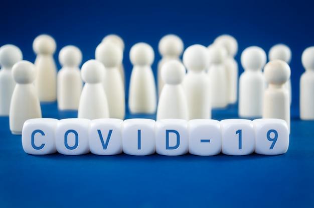Covid-19 napisany na białych klockach przed drewnianymi figurkami przedstawiającymi ludzkie społeczeństwo w koncepcyjnym wizerunku wirusa zagrażającego zdrowiu.