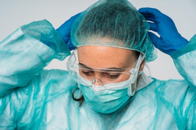 Covid-19 pandemia koronawirusa, lekarz zakładający maskę medyczną, okulary, lateksowe rękawiczki i odzież ochronną przed wirusem
