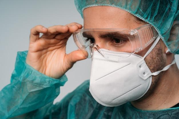 Covid-19 pandemia koronawirusa, lekarz zakładający okulary, maskę medyczną, okulary, rękawiczki lateksowe i odzież ochronną przed wirusem
