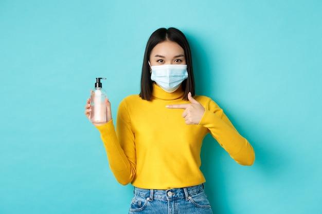 Covid-19, pojęcie dystansu społecznego i pandemii. wesoła azjatycka kobieta pokazująca środek do dezynfekcji rąk, zaleca stosowanie środka antyseptycznego z koronawirusa, nosząc maskę medyczną