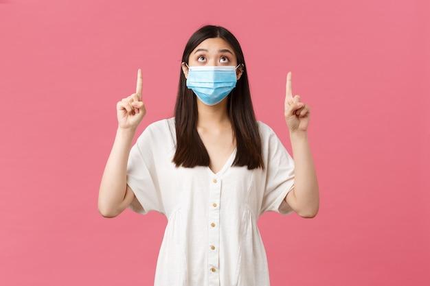 Covid-19, pojęcie dystansu społecznego, wirusa i stylu życia. ciekawa ładna azjatycka dziewczyna w masce medycznej i letniej sukience, patrząc i wskazując palcem na promo, reklamę, różowe tło.
