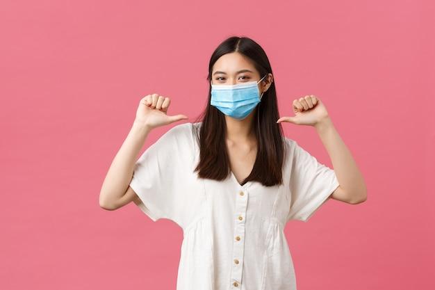 Covid-19, pojęcie dystansu społecznego, wirusa i stylu życia. dumna i pewna siebie azjatka chwaląca się osobistymi osiągnięciami, ubrana w ochronną maskę medyczną i letnią sukienkę, wskazującą na siebie.