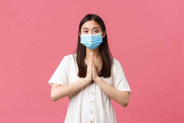 Covid-19, pojęcie dystansu społecznego, wirusa i stylu życia. nadzieja śliczna azjatka w masce medycznej prosząca o pomoc lub błagająca o łaskę z brakiem entuzjazmu, poważną ponurą twarzą, błagającym różowym tłem.