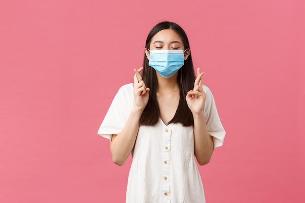 Covid-19, pojęcie dystansu społecznego, wirusa i stylu życia. pełna nadziei rozmarzona azjatycka dziewczyna składa życzenia, zamyka oczy i uśmiecha się w masce medycznej, trzyma kciuki powodzenia, błagając na różowym tle.