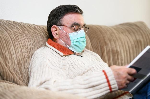 Covid- 19. starszy mężczyzna z ochronną maską twarzową, czytający książkę, podczas kwarantanny w domu.