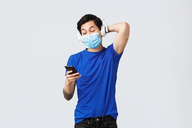 Covid-19 styl życia, emocje ludzi i wypoczynek na koncepcji kwarantanny. beztroski przystojny azjatycki mężczyzna wybierający muzykę z listy odtwarzania, używający telefonu komórkowego jako cieszącego się piosenką ze słuchawkami