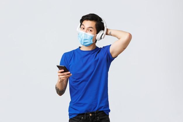 Covid-19 styl życia, emocje ludzi i wypoczynek na koncepcji kwarantanny. przystojny młody queer azjatycki facet w masce medycznej i słuchawkach, słuchający muzyki, używający telefonu komórkowego