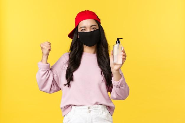 Covid-19, styl życia zdystansowany społecznie, zapobieganie koncepcji rozprzestrzeniania się wirusa. wesoła azjatka w masce na twarz podczas koronawirusa poleca produkt higieniczny, pokazując środek do dezynfekcji rąk, żółte tło.