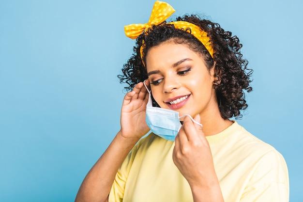 Covid-19, wirus zakaźny. bliska strzał młodej czarnej kobiety afroamerykanów z kręconymi krzaczastymi włosami, nosi jednorazową maskę medyczną