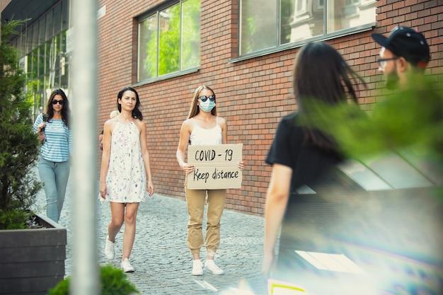 Covid-19, zachowaj dystans. koleś ze znakiem - kobieta stoi protestując przeciwko rzeczom, które ją denerwują. samotna demonstracja prawa do swobodnej rozmowy na ulicy ze znakiem. opinia publiczna. pandemia, ochrona.
