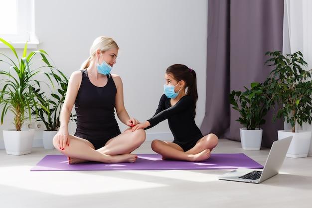 Covid-19 zamknięcie. matka i córka w kwarantannie robi joga w pomieszczeniu. matka i córka robią medytację podczas blokady. zdrowie, aktywność fizyczna pozostań w domu i dbaj o siebie w przypadku izolacji koronawirusa.