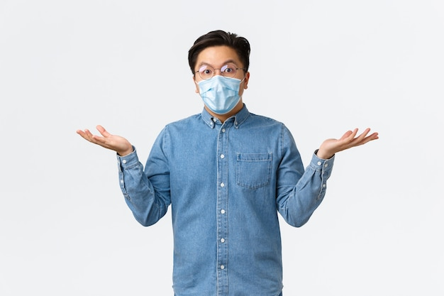 Covid-19, zapobieganie wirusom i koncepcja dystansu społecznego w miejscu pracy. zdezorientowany i zaskoczony azjatycki przedsiębiorca mężczyzna rozłożył ręce na boki i wzruszył ramionami, zdziwiony, założył maskę medyczną i okulary.