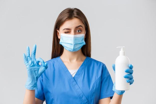 Covid-19, zapobieganie wirusom, pracownikom służby zdrowia i koncepcja kwarantanny. pewna siebie urocza pielęgniarka lub lekarz w niebieskich fartuchach, masce medycznej i rękawiczkach, zatwierdza i poleca mydło lub środek do dezynfekcji rąk
