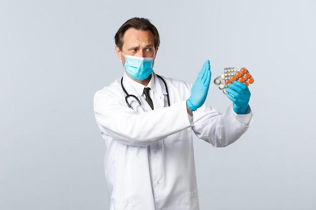 Covid-19, zapobieganie wirusom, pracownikom służby zdrowia i koncepcja szczepień. poważny niezadowolony lekarz zabrania używania tych tabletek, okazywania gestu braku lub zatrzymania, mówiąc o lekach, noszenia maski medycznej