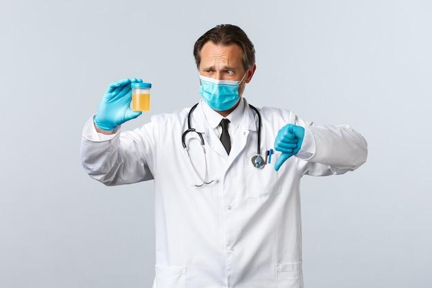 Covid-19, zapobieganie wirusom, pracownikom służby zdrowia i koncepcja szczepień. rozczarowany lekarz w masce medycznej i rękawiczkach pokazuje próbkę moczu, kciuk w dół ma zły wynik testu, białe tło