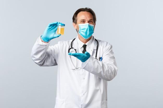 Covid-19, zapobieganie wirusom, pracownikom służby zdrowia i koncepcja szczepień. zadowolony uśmiechnięty lekarz w masce medycznej i rękawiczkach pokazuje próbkę moczu, zadowolony z czystego wyniku testu, białe tło