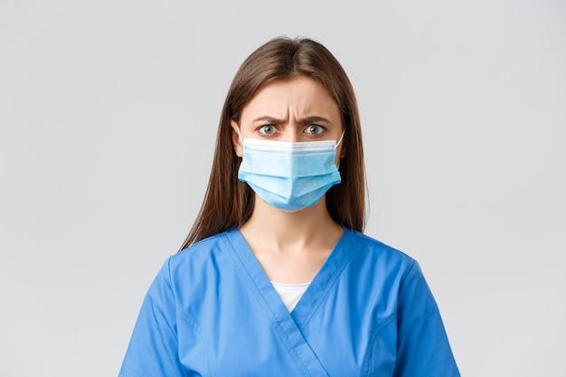 Covid-19, zapobieganie wirusom, służbom zdrowia, pracownikom służby zdrowia i koncepcji kwarantanny. zła lub sfrustrowana pielęgniarka reagująca na złe wieści. zawiedziony lekarz w niebieskich fartuchach i masce medycznej