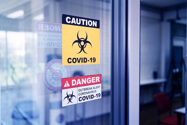 Covid-19 znaki ostrzegawcze przyklejają się do szklanych drzwi.