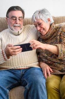 Covid-19 zostaje w domu. szczęśliwa emerytowana starsza para, robi rodzinnej rozmowie wideo z telefonem komórkowym. dystans społeczny, pozytywny wyraz.