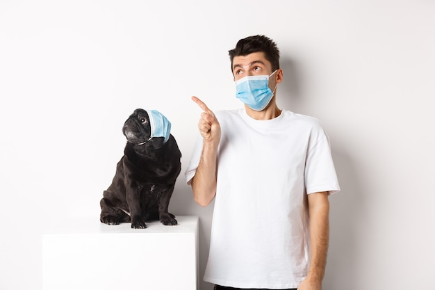 Covid-19, zwierzęta i koncepcja kwarantanny. młody mężczyzna i czarny pies w maskach medycznych, mops i właściciel patrząc w lewy górny róg, biały