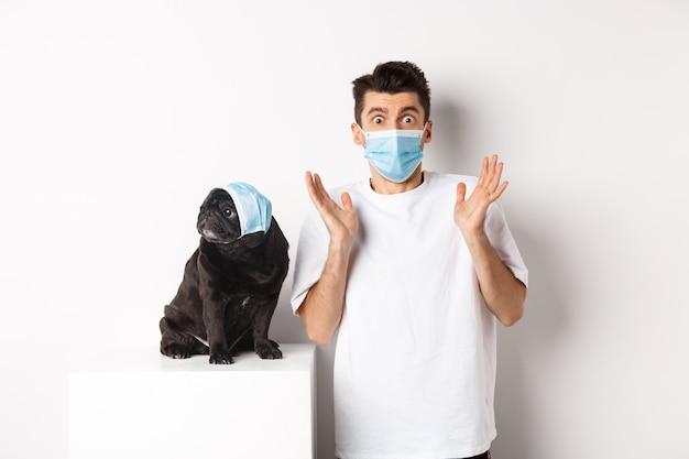Covid-19, zwierzęta i koncepcja kwarantanny. zszokowany właściciel psa i mops w maskach medycznych, wpatrzony w kamerę zdumiony, stojący nad bielą