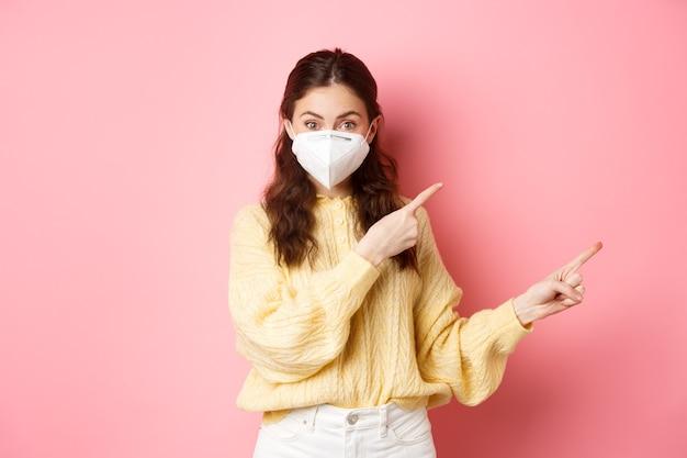 Covid corona i koncepcja dystansowania społecznego podekscytowana modelka w respiratorze pokazuje punkty reklamowe przy logo na boku, nosi medyczny respirator na różowej ścianie twarzy