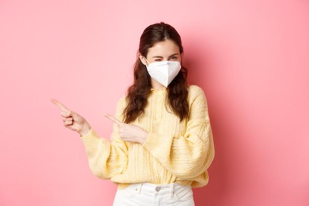 Covid corona i koncepcja dystansu społecznego zalotna młoda kobieta zaprasza do zapoznania się z ofertą specjalną, mrugając do ciebie w respiratorze medycznym, wskazując palcami na bok tekst promocyjny różowa ściana